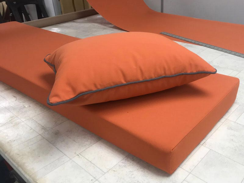 A set of new bespoke outdoor cushions covered in a contemporary orange fabric with grey piping