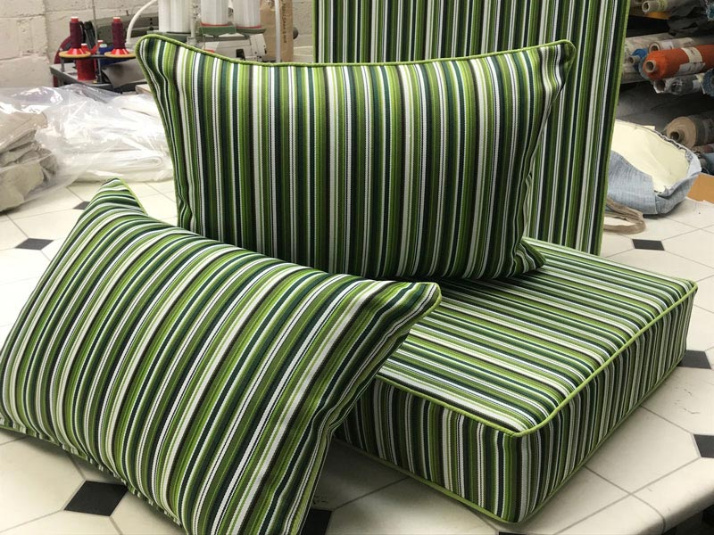 A set of new bespoke outdoor cushions covered in a contemporary stiped fabric