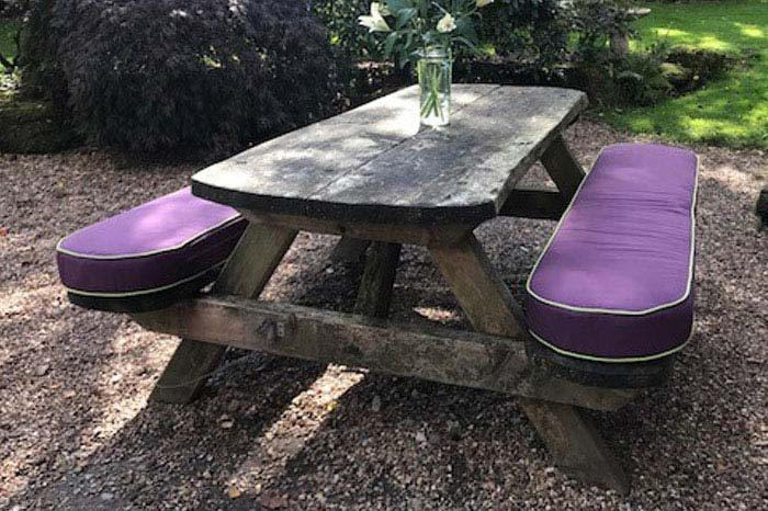 Bespoke outdoor cushions upgrade a wooden picnic bench